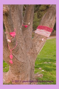 The trunk and base branches of a large tree yarn bombed in Griffith Park.  One large branch is encricled with a pink and red two stripped band and other branches have knitted hears in pink and red hanging off of them.